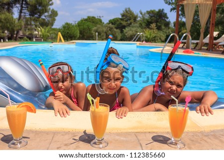 Girls drinking juice in the swimming pool