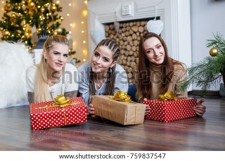 Girls friends decorating fur-tree near fireplace with candles and gifts. girls  dreaming. New year's eve. Christmas eve. Cozy holiday at the fur-tree with lights and gold decor. #759837547