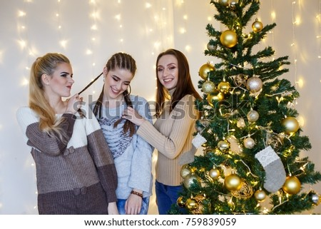 Girls friends decorating fur-tree near fireplace with candles and gifts. girls  dreaming. New year's eve. Christmas eve. Cozy holiday at the fur-tree with lights and gold decor. #759839059