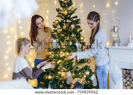 Girls friends decorating fur-tree near fireplace with candles and gifts. girls  dreaming. New year's eve. Christmas eve. Cozy holiday at the fur-tree with lights and gold decor. #759839062