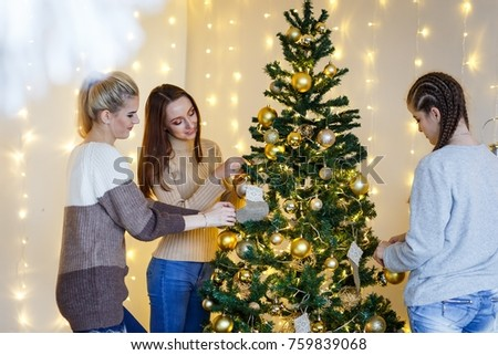 Girls friends decorating fur-tree near fireplace with candles and gifts. girls  dreaming. New year's eve. Christmas eve. Cozy holiday at the fur-tree with lights and gold decor. #759839068