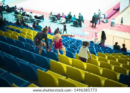 Girls gymnasts in suits are going downstairs, climbing over the sports arena seats. Funny picture.