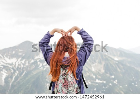 Girls hand to make a heart shape. Copyspace. A young pretty redheaded woman standing on a background of mountains. Trekking, vacation and tourism concept. Copyspace