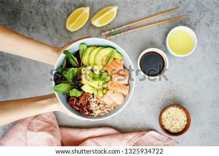 Girls' hands holding salmon poke bowl Salmon poke bowl with salad, avocado, edamame beans, pineapple, sesame and brown rice Traditional Hawaiian dish