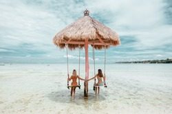 Girls hanging on swing on tropical beach on paradise Bali island