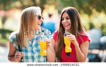 Girls have fun. Two young girls enjoys in a good mood, having fun together in the city. Lifestyle concept