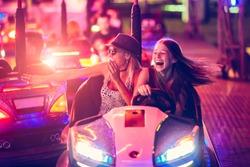 Girls having fun in electric bumper car in amusement park
