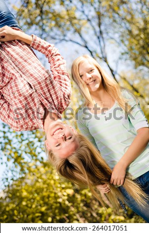Girls having fun in park hanging upside down on green copy space background