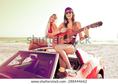 girls having fun playing guitar on th beach with a convertible car #288444662
