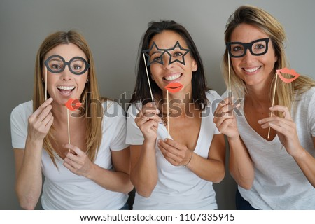 Girls having fun playing with photobooth props