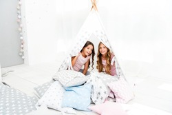 Girls having fun tipi house. Girlish leisure. Sisters share gossips having fun at home. Cozy place tipi house. Sisters or best friends spend time together lay in tipi house. Pajamas party for kids.