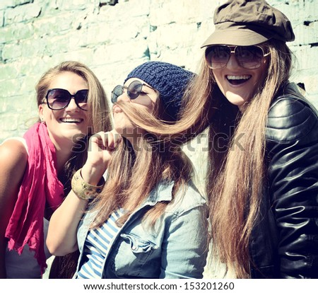 Girls having fun together outdoors and making moustache of hair lifestyle theme toned