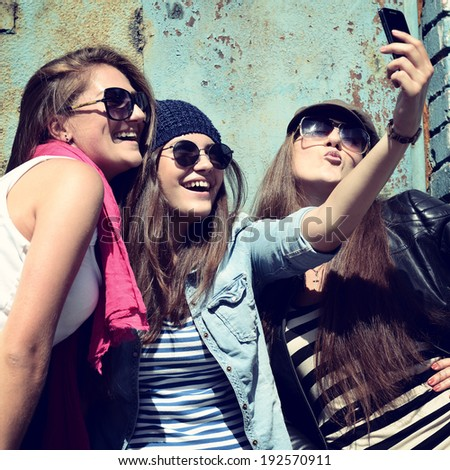 Girls having fun together outdoors and making photo with smart phone lifestyle toned