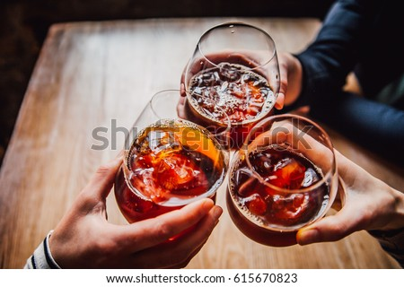 Girls having good time,cheering and drinking cold drinks, enjoying friendship together in coffee shop, close up view on hands
