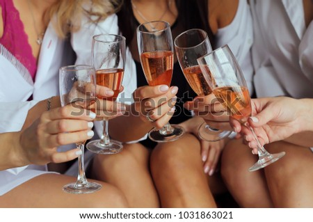 Girls  hold in hands glasses with champagne, friends celebrating and toasting #1031863021