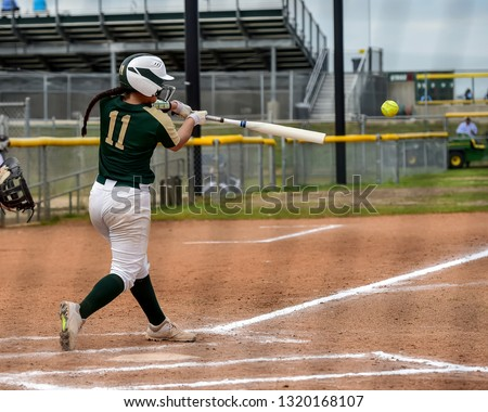 Girls in action playing in a softball game
