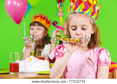 Girls in birthday crowns playing with party horns