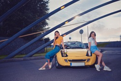 Girls in casual outfit eating hamburgers and holding beverages in paper cups while leaning on the hood of yellow car roadster. Fast food. Copy space