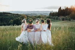 Girls in dresses and wreaths of flowers and greenery are in the green field at sunset