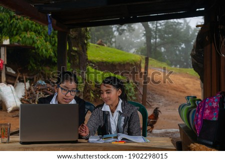 Girls in rural areas receive distance education, using a laptop. Foto stock ©