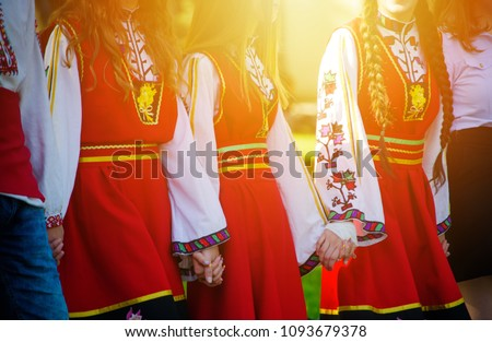 Girls in traditional Bulgarian costumes with red dresses and patterns on white shirts holding hands in the sunset. Concept of unity