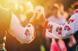 Girls in traditional Bulgarian ethnic costumes with red dresses and patterns on white shirts holding hands in the sunset. Concept of unity. Celebration