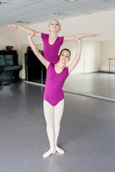 Girls learn support in choreography.