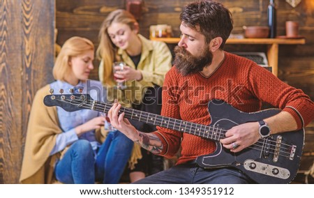 Girls listening to song performed by handsome bearded musician. Guitarist entertaining guests at party. Man with hipster beard playing electrical guitar. Bearded man united with his instrument. #1349351912
