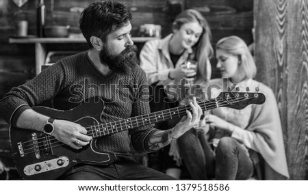 Girls listening to song performed by handsome bearded musician. Guitarist entertaining guests at party. Man with hipster beard playing electrical guitar. Bearded man united with his instrument. #1379518586
