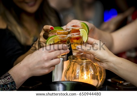 Girls making a toast with tequila shots