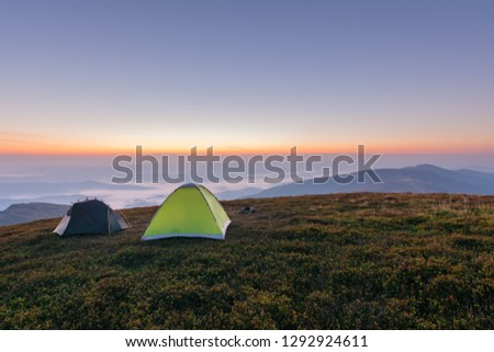 Girls on a mountain ridge rest with tents. #1292924611
