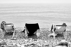 Girls on deck chairs on a pebble beach by the Aegean Sea in Greece,monochrome