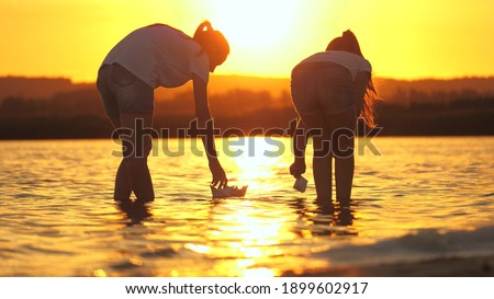 Girls play with paper boats. Child's hands launches a boat in park into river. Paper fleet. Children put a paper boat into water. Happy family fantasy, childhood dream, adventure and travel concept. ストックフォト ©