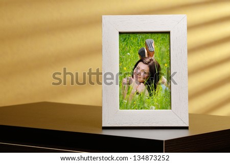 Girls portrait in a photo frame, standing on a table