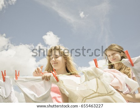 girls putting washing on a line