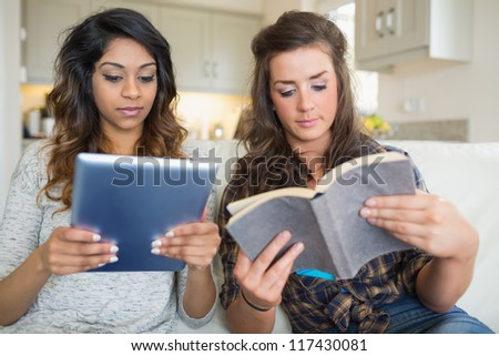 Girls reading a book and holding a tablet computer while sitting on a couch