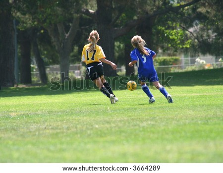 Girls running after a ball playing soccer