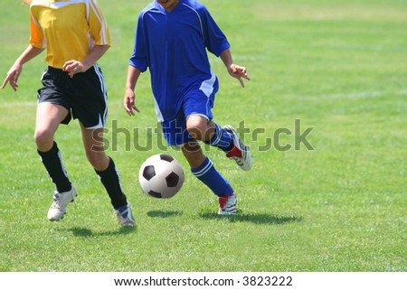 Girls running after the ball in a soccer match
