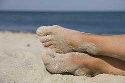 Girls sandy feet on beach in front of the open sea in summer