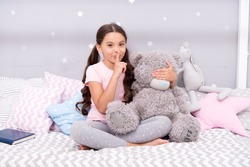 Girls secret. Cute kid show silence finger gesture. Little secret. Small girl play with teddy bear in bed. Keeping mouth shut. Being quiet. Silence and shushing. Top secret. Can you keep secret.