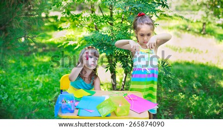 Girls, sisters, kids, friends cutting multicolored paper outdoors, classroom playing in the garden. Focus on elder girl\'s face, and on younger girl\'s hand with scissors