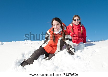 Girls sitting and smiling in snow at sunny day - winter fun
