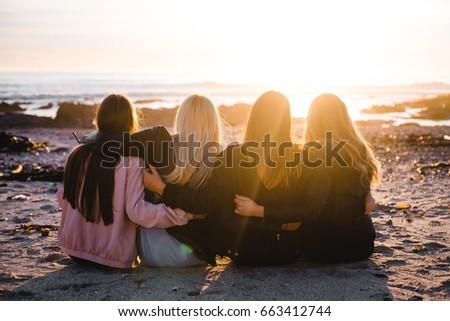 Girls sitting on beach watching sunset