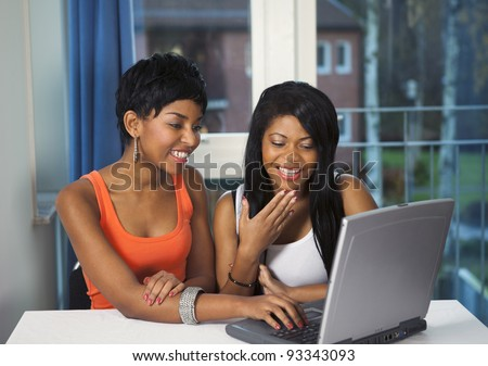 Girls socializing or chatting on internet laughing and having fun - stock photo