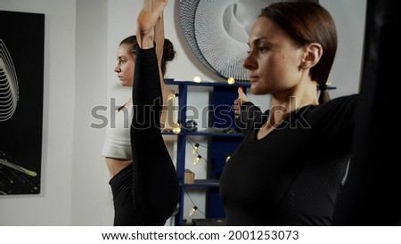 Girls stretching one leg up to do Utthita Hasta Padangustasana pose Foto stock ©