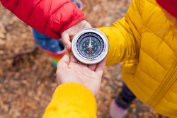 Girls Toddler holding compass in the hands. Children exploring nature in the forest on warm autumn day Kids learning how to use compass. Outdoor recreation and awesome adventures with children in fall