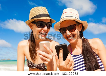 Girls using smart phone on the beach. Technology and beach concept. Summer holiday