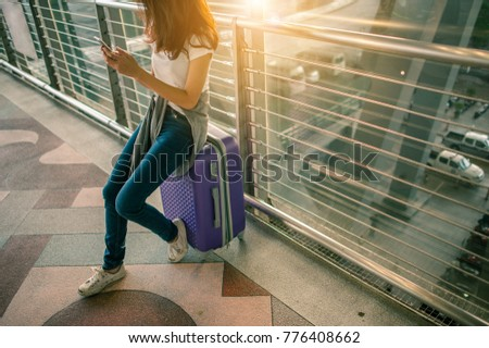 girls using smartphone checking flight or online check-in at airport together, with luggage. Air travel, summer holiday, or mobile phone application  #776408662