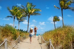 Girls waking  to the beach. Footpath with palm trees, and ocean in the background.South Beach, Miami, Florida, USA