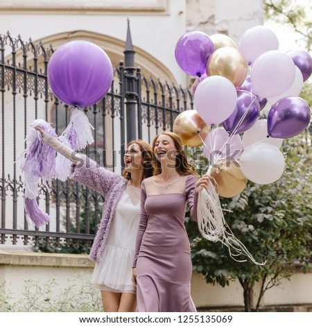 girls walk around the city with balloons, girlfriends laugh, girls with balloons, girlfriends blonde and redhead, girlfriends with purple, golden balloons